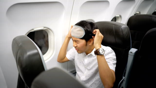man sleeping on airplane with eye cover sleep masks - sitting stock videos & royalty-free footage
