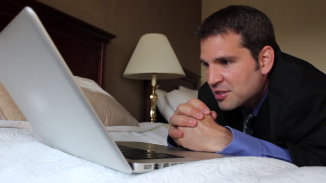 CU Man sleeping on bed talking to family on laptop / Portland, ME, United States