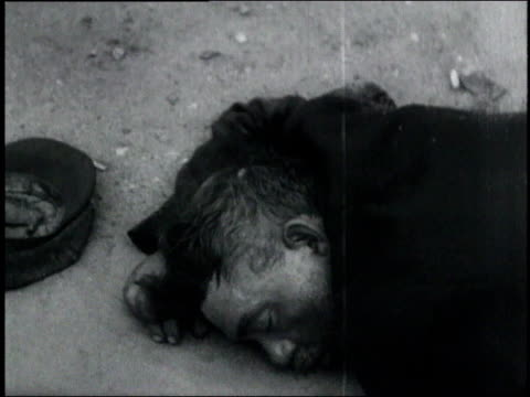man sleeping on the ground his hat fallen off / usa - 1932 stock-videos und b-roll-filmmaterial