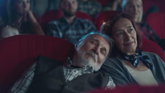 mann schläft auf der schulter von frauen im kino - paar gruppierung stock-videos und b-roll-filmmaterial