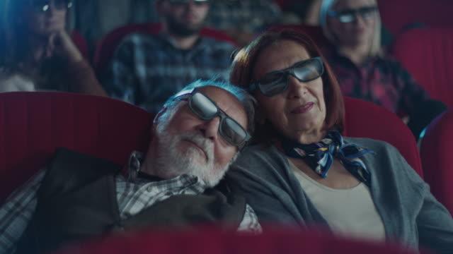 man sleeping on women's shoulder in cinema - 3d glasses stock videos & royalty-free footage