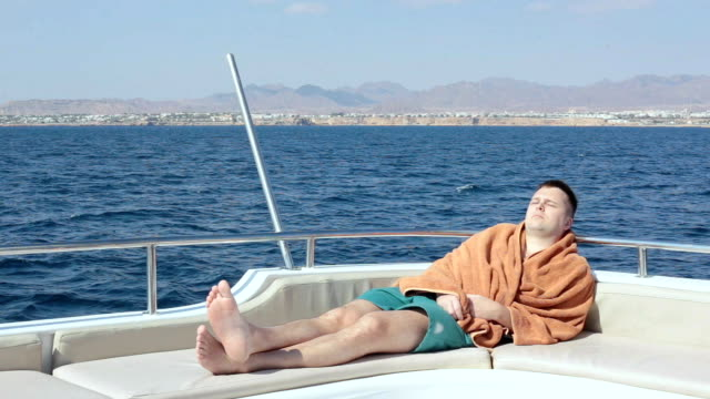 a man sleeps at the stern of a yacht. - one mid adult man only stock videos & royalty-free footage