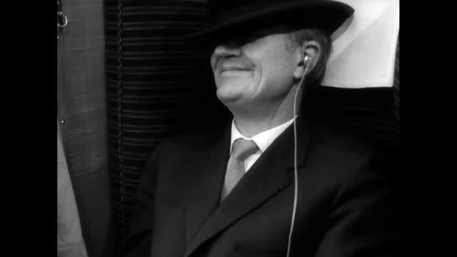vidéos et rushes de man sleeps on train listening to music with hat over eyes; 1963 - wagon