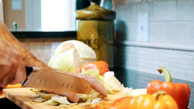 男は新鮮なサラダのためにキャベツをスライス - オレンジピーマン点の映像素材/bロール