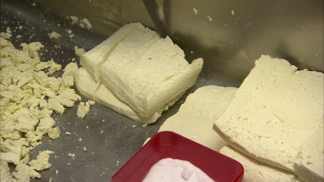 man slicing cheese in a big metal sink - feta stock videos & royalty-free footage