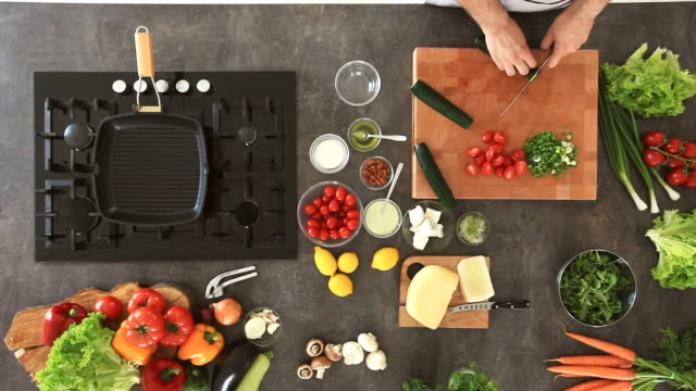 vídeos y material grabado en eventos de stock de hombre cortando pepino en la tabla de cortar, preparar una ensalada de verduras - picar preparar comida