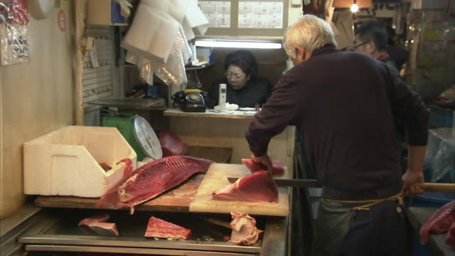 ms man slicing fish in tsukiji fish market, tokyo, japan - ファーマーズマーケット点の映像素材/bロール