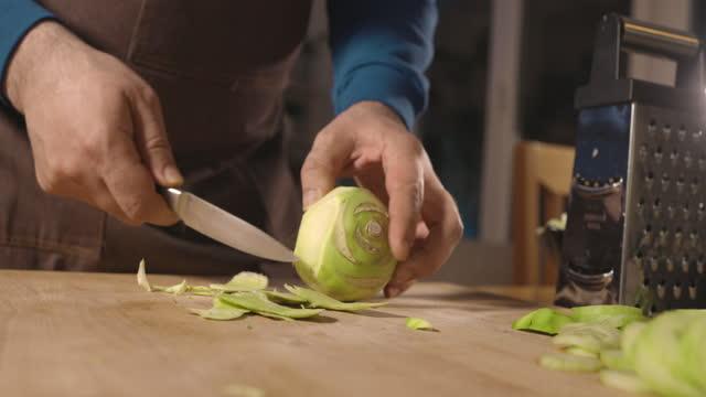 vídeos de stock, filmes e b-roll de homem cortando kohlrabi em tábua de corte na cozinha - braço humano