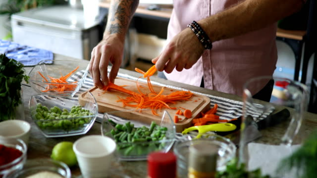 man slicing the carrots into long, thin strips with a julienne peeler - antioxidant stock videos & royalty-free footage