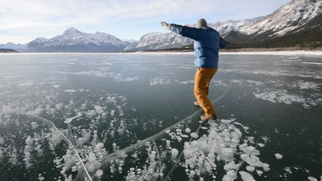 Man slides across frozen lake surface, mountains distant