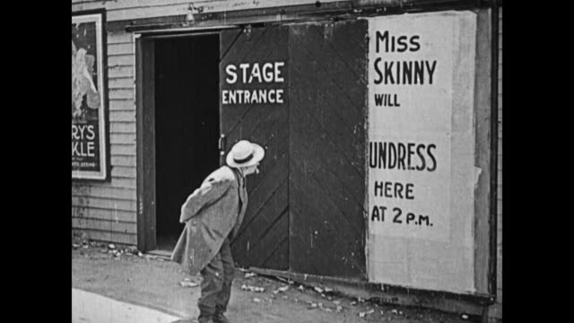 "1919 man (fatty arbuckle) slides open a stage entrance door, partially covering the poster for ""the little laundress"",  leaving what remains to read ""miss skinny will undress here at 2pm"" / man exits and looks at poster - fatty arbuckle stock videos and b-roll footage"