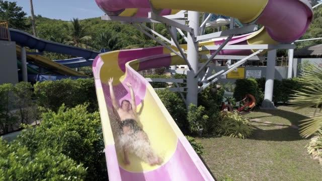 vídeos de stock, filmes e b-roll de homem de deslizar para baixo a água desliza num parque aquático - tobogã d'água