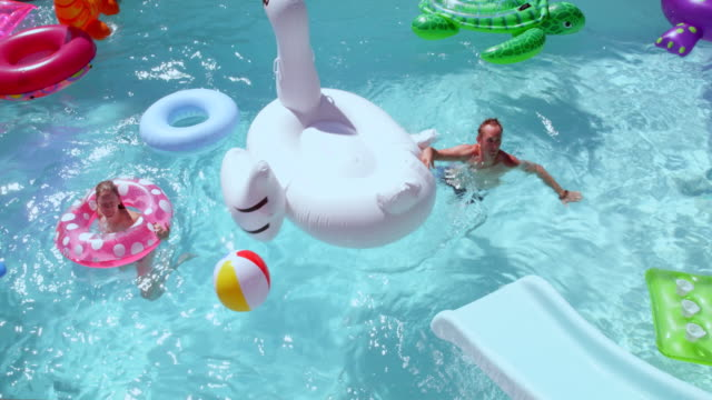 MS SLO MO Man sliding head first down water slide onto large inflatable pool toy in outdoor pool on summer afternoon
