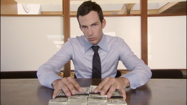 ms, man sliding stack of cash across table, portrait, los angeles, california, usa - deception stock videos and b-roll footage