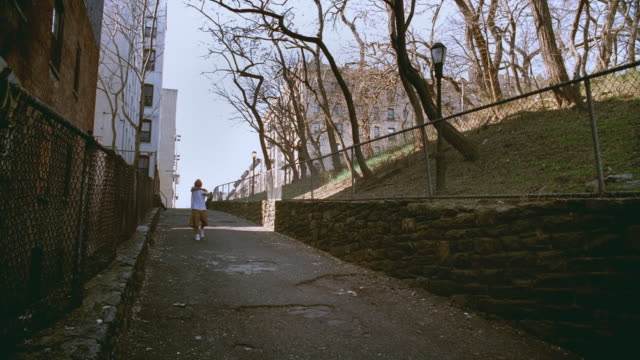 WS Man sloped alleyway next to park, tossing basketball around and doing various tricks/ Harlem, New York