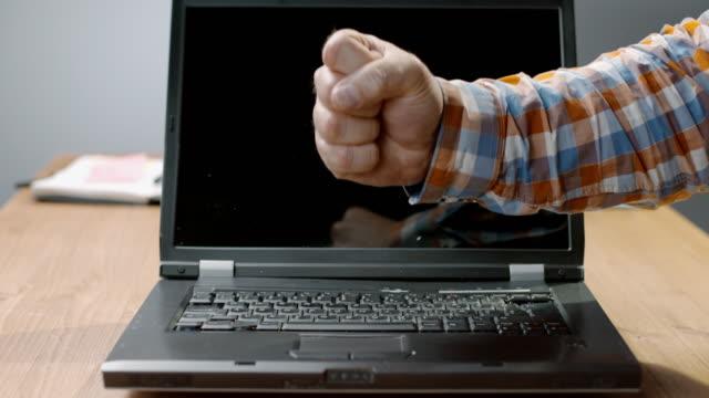 SLO MO LD Mann einen Laptop mit der Faust zertrümmern und ihn zu zerbrechen