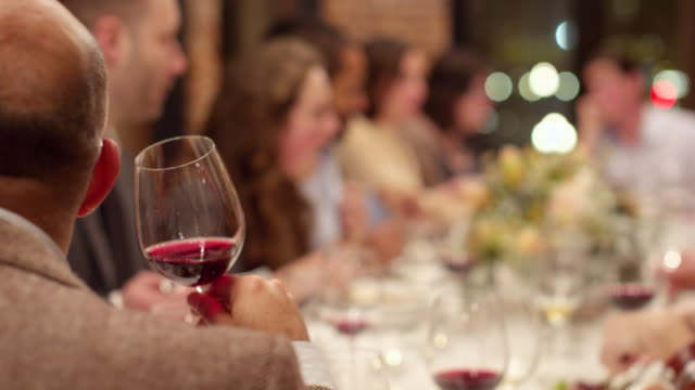 MS CU Man smelling and drinking wine during dinner party with friends
