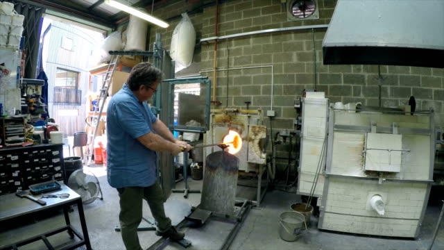 vídeos de stock, filmes e b-roll de man smelting glass in furnace - fundir técnica de vídeo