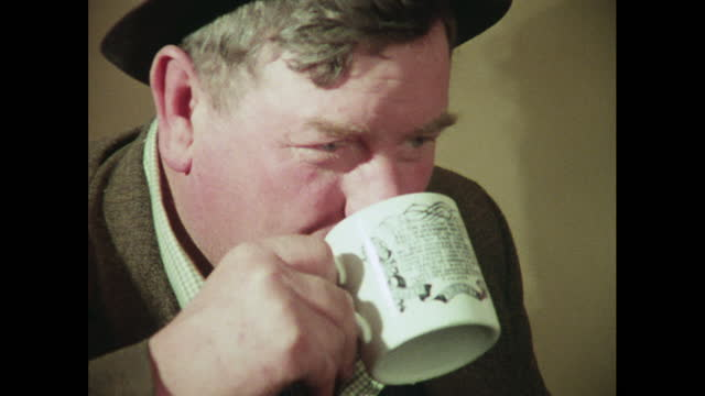 man smiles and drinks from a mug, 1970s - one man only stock videos & royalty-free footage