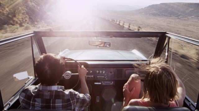 ms man smiling driving convertible off road vehicle on rural desert road woman riding in passenger seat - オープンカー点の映像素材/bロール