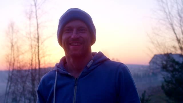 Man smiling to a camera. Spring sunset