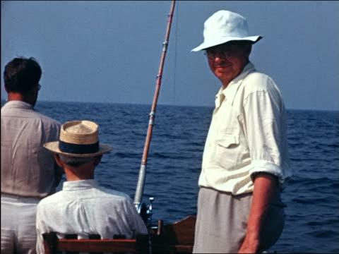 vidéos et rushes de 1941 home movie rear view man smiling to camera as others deep sea fish off end of boat - seulement des hommes d'âge mûr