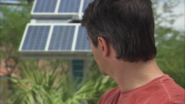 vidéos et rushes de cu man smiling with solar panel in background in springs preserve / las vegas, nevada, usa - seulement des hommes
