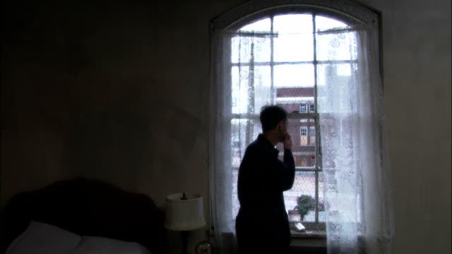 vidéos et rushes de a man smokes a cigarette as he looks out a window. - manque