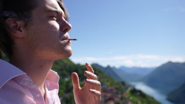 男は視点でタバコを吸い、太陽の下でリラックス - マッチ箱点の映像素材/bロール