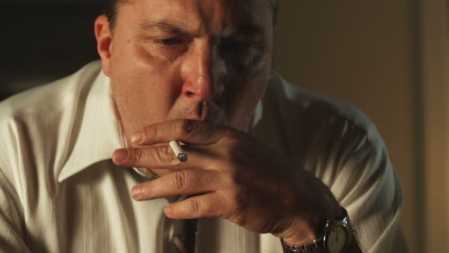 vidéos et rushes de man smoking a cigarette while coughing - 45 49 ans