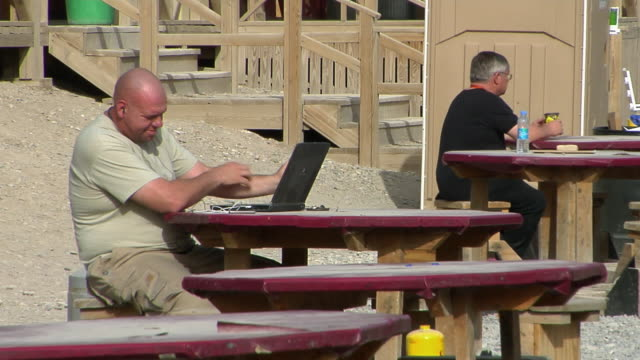 vídeos de stock e filmes b-roll de ms man smoking cigar and using laptop outdoors / kandahar afghanistan - kandahar