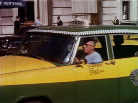 1960 PAN man smoking cigar driving taxi on city street / NYC / newsreel