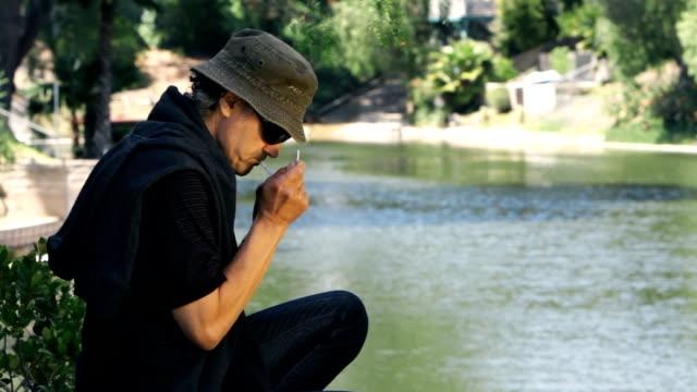 man smoking cigarette by lake - no smoking sign stock videos & royalty-free footage