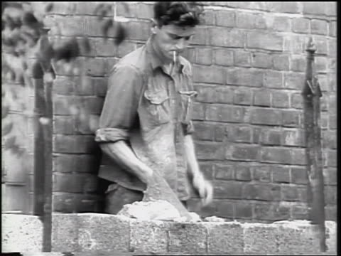 b/w 1961 man smoking cigarette laying bricks for berlin wall / germany / cold war / newsreel - 1961 stock-videos und b-roll-filmmaterial