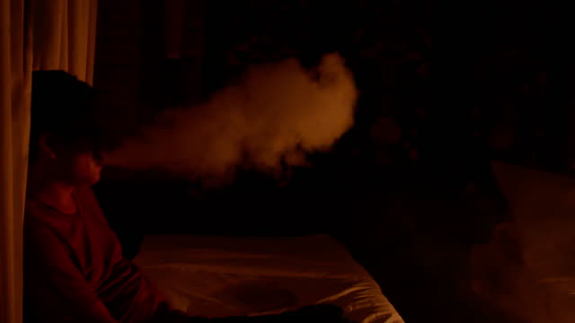 暗い部屋で男喫煙電気電子タバコの蒸気 - 煙草製品点の映像素材/bロール