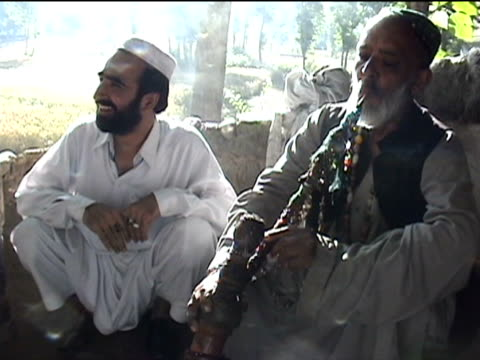 vídeos de stock e filmes b-roll de ms man smoking hashish with waterpipe swat district in tribal zone at afghan border pir baba village federally administered tribal areas pakistan... - fotografia de três quartos