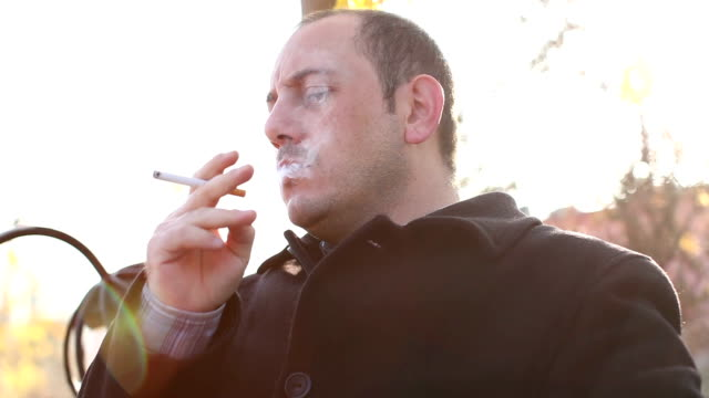 man smoking sigarette and waiting for someone - smoking issues stock videos & royalty-free footage