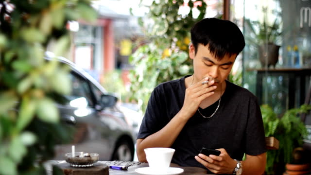 man smoking while using smart phone and drink coffee