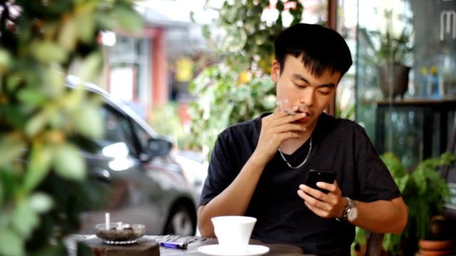 man smoking while using smart phone and drink coffee - coffee drink stock videos & royalty-free footage