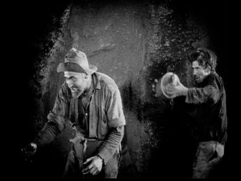 vídeos y material grabado en eventos de stock de 1926 b/w ms man (danny hoy) sneaking up on another man (frank brownlee) and hitting him over head with ceramic pot / usa - 1926
