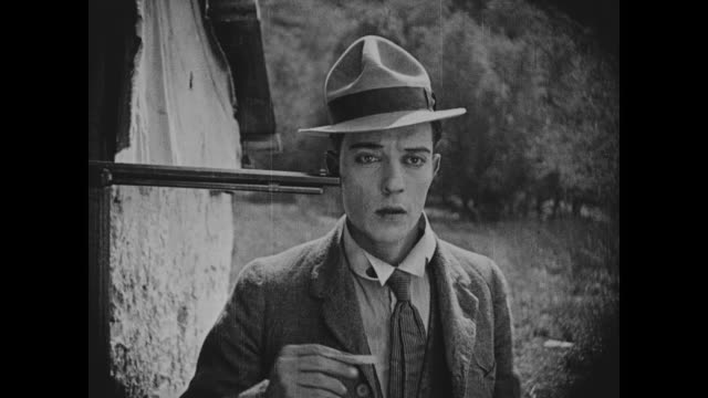 1918 man (buster keaton) sneezes tobacco into rifle-wielding man's (al st. john) eyes - stereotypical stock videos & royalty-free footage