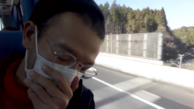 man sneezing on bus . - asian man coughing stock videos & royalty-free footage