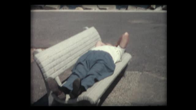 vidéos et rushes de 1963 man snoozing on park bench - banc