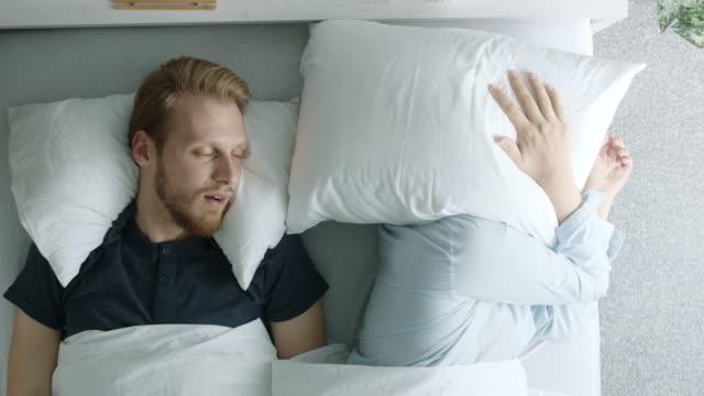 vídeos de stock, filmes e b-roll de ronco de homem e sua esposa cobrindo a cabeça com travesseiro - casal jovem