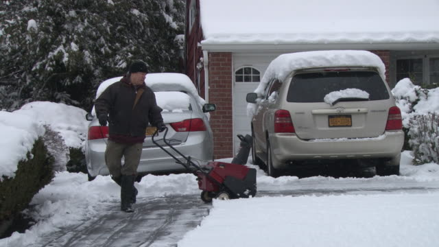 man snow blows his driveway and walkway in a suburban home in westchester county , ny, suburbs of new york city / this snow storm, which dropped... - occurrence stock videos & royalty-free footage