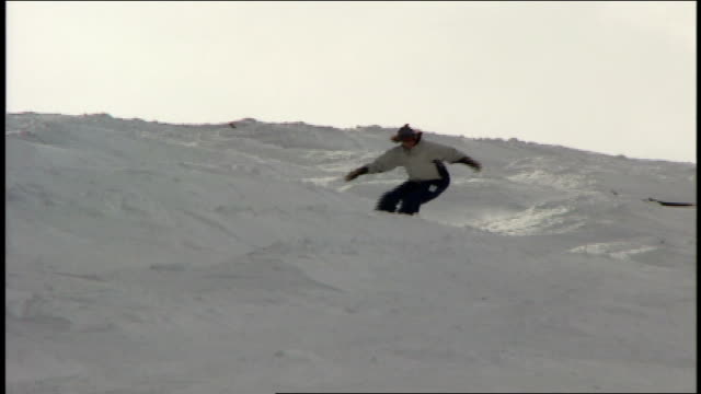 vídeos de stock e filmes b-roll de man snowboarding down hill and doing tricks in telluride colorado - roupa de esqui