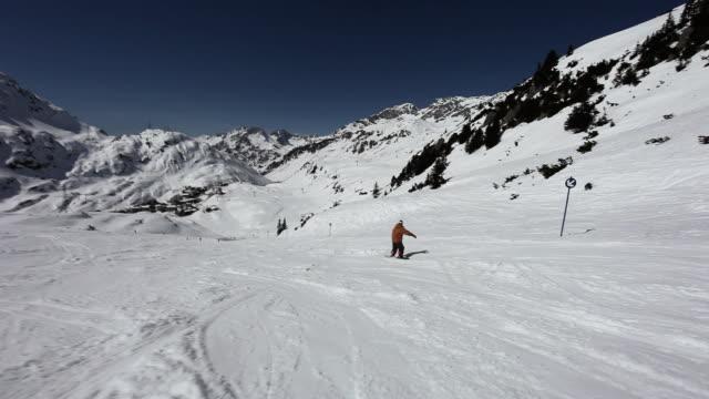 vídeos y material grabado en eventos de stock de man snowboarding in ski resort - vacaciones en la nieve