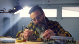 SLO MO Man soldering a circuit board in his home workshop