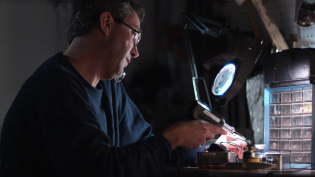 stockvideo's en b-roll-footage met cu, man soldering at workbench and talking on phone, hollywood, california, usa - draadloze telefoon