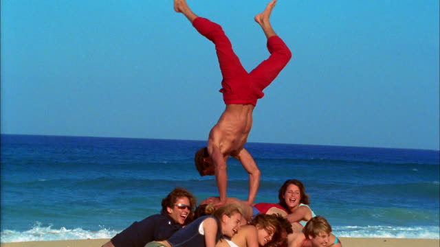 a man somersaults over a group of young adults huddled on a beach. - pyramid stock videos and b-roll footage